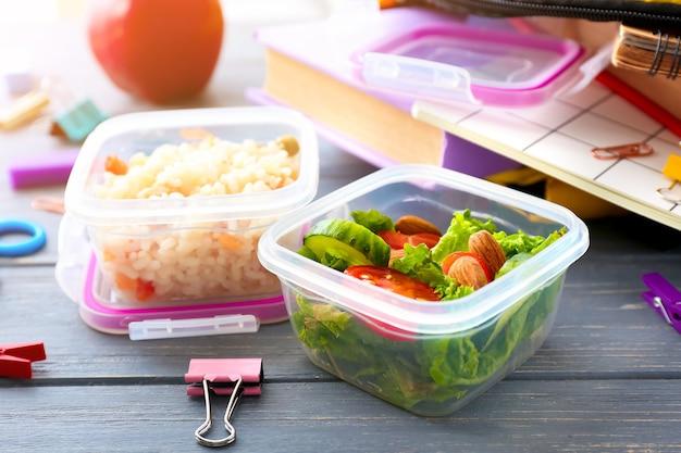 Schulbrotdosen mit leckerem essen und schreibwaren auf holz