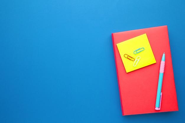 Schulbücher mit stift auf blauer wand mit kopienraum