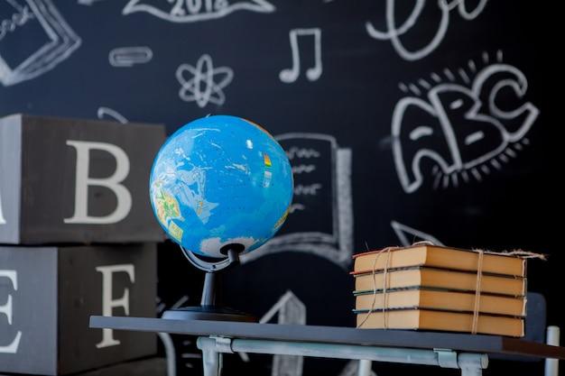 Schulbücher und weltkugel auf schulbank