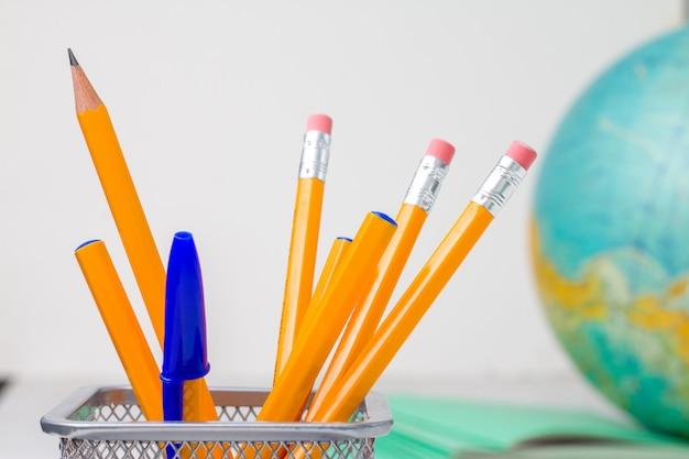 Schulbüro liefert bleistifte kugelschreiber in standpapier zusammensetzung notizbuch und globus