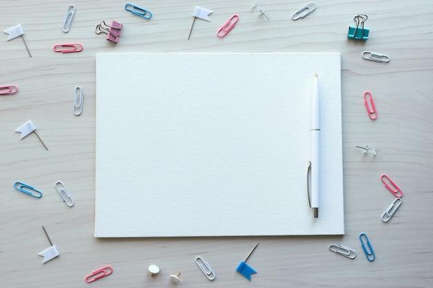 Schulbürobedarf auf hölzernem hintergrund. zurück zum schulkonzept. weiße tafel mit händen für kopierraum. draufsicht bereit für ihr design.