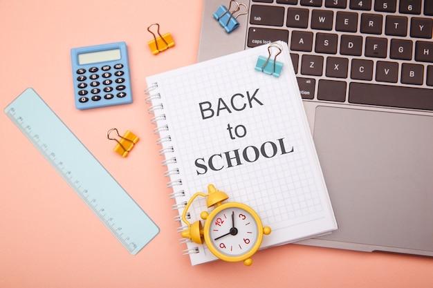 Schulbürobedarf auf pink und notizbuch mit back to school.