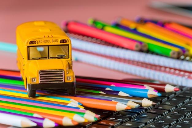 Schulbus auf farbstiften und tastatur, zurück in die schule