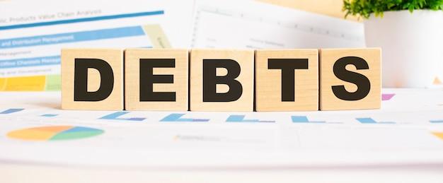Schulden das wort auf holzwürfeln geschäftsdiagramm