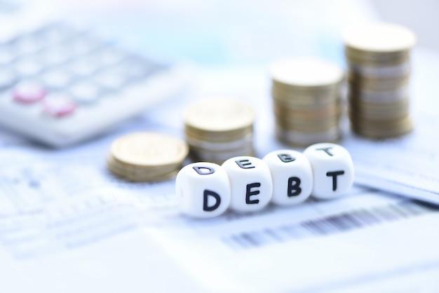 Schuldenkonzept-taschenrechnerstapelmünze auf rechnungsrechnungspapier