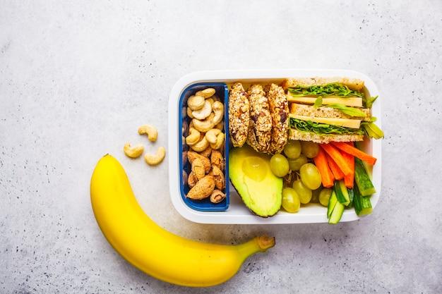 Schule gesunde brotdose mit sandwich, keksen, früchten und avocado auf weißem hintergrund.