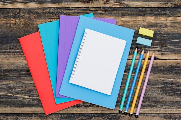 Schule nach pandemiekonzept mit notizbüchern, bleistiften, lesezeichenaufklebern auf holztisch flach lag.