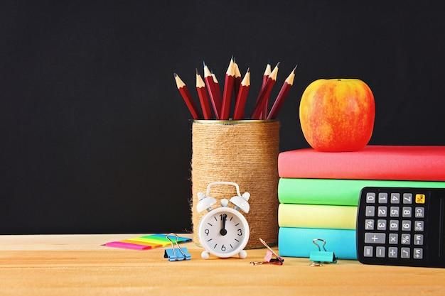 Schule und büroartikel auf einem schwarzen tafelhintergrund. zurück zur schule.