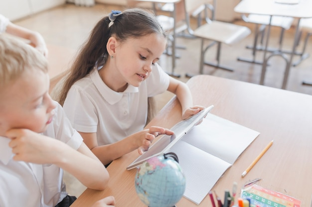 Schulemädchen, das tablette nahe jungen verwendet