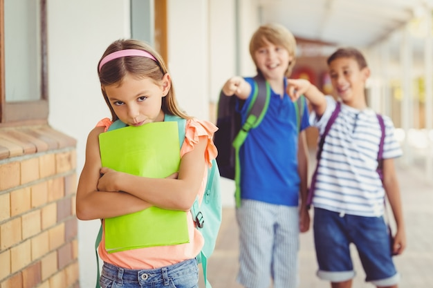 Schulfreunde, die ein trauriges mädchen im korridor einschüchtern