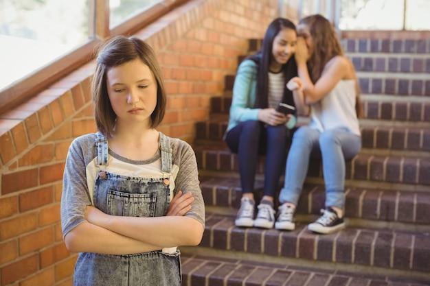 Schulfreunde, die ein trauriges mädchen im schulkorridor schikanieren