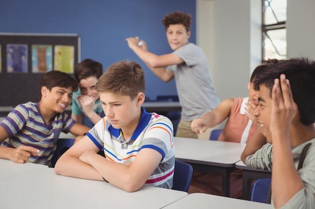 Schulfreunde, die einen traurigen jungen im klassenzimmer schikanieren