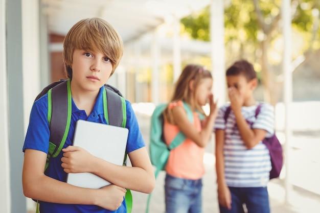 Schulfreunde, die einen traurigen jungen im korridor einschüchtern