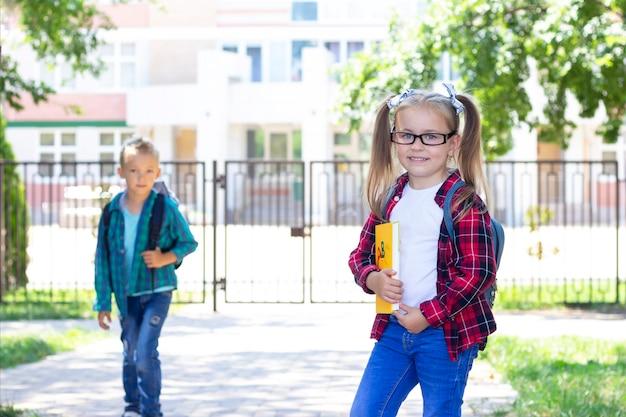 Schulfreunde mit rucksäcken grüßen. schuljunge und schulmädchen lächeln