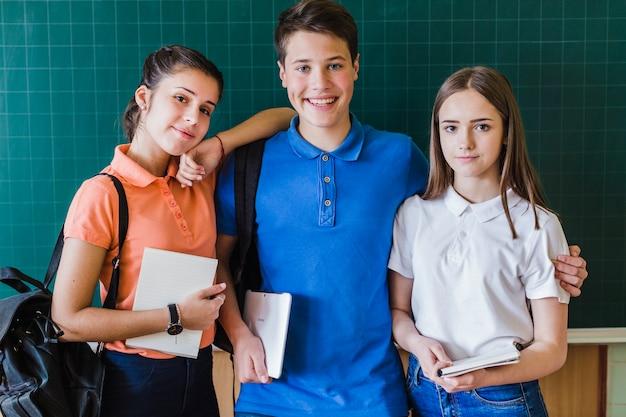 Schulfreunde posieren vor der tafel
