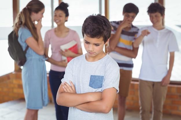 Schulfreunde schikanieren einen traurigen jungen im korridor