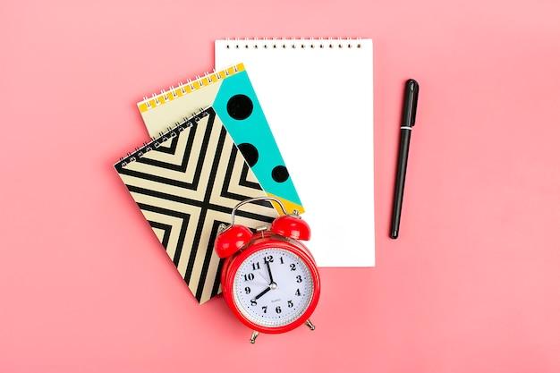 Schulgegenstände wie geometrische notizbücher, stift und wecker auf rosa