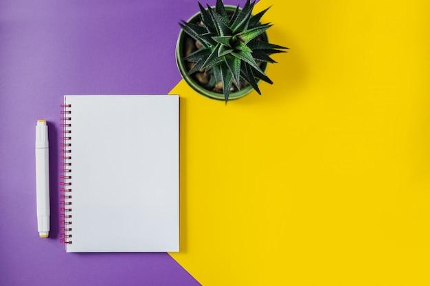 Schulheft auf gelbem und purpurrotem, gewundenem notizblock auf einer tabelle. draufsichthintergrund mit copyspace. büro notizblock flach zu legen.