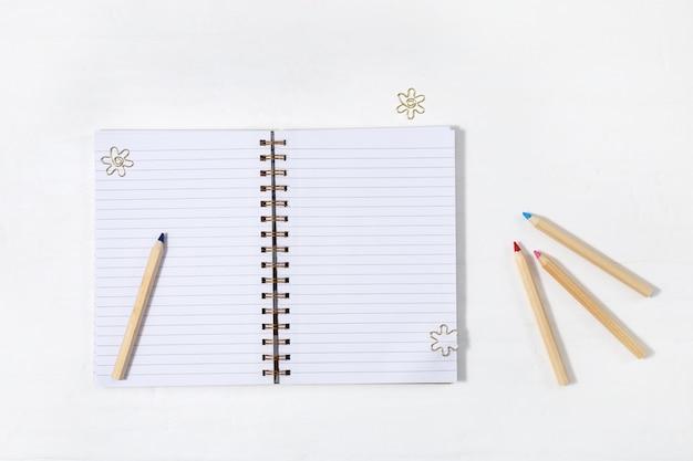 Schulheft mit metallklammern. öffnen sie notizbuch auf frühling mit sauberen gezeichneten blättern und hölzernem farbigem bleistift auf hellem arbeitsplatz. zurück zum schulkonzept. ansicht von oben.