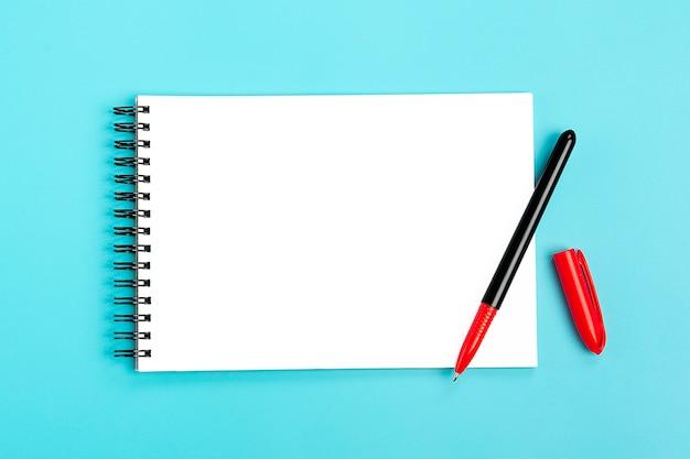 Schulheft und roter stift auf einem blauen, gewundenen notizblock auf einer tabelle