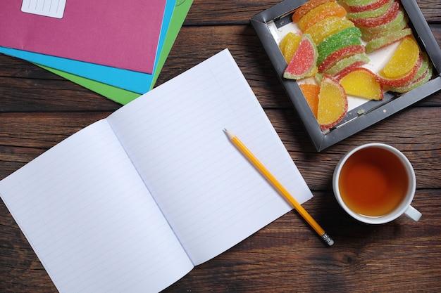 Schulhefte, eine tasse tee und bunte marmelade