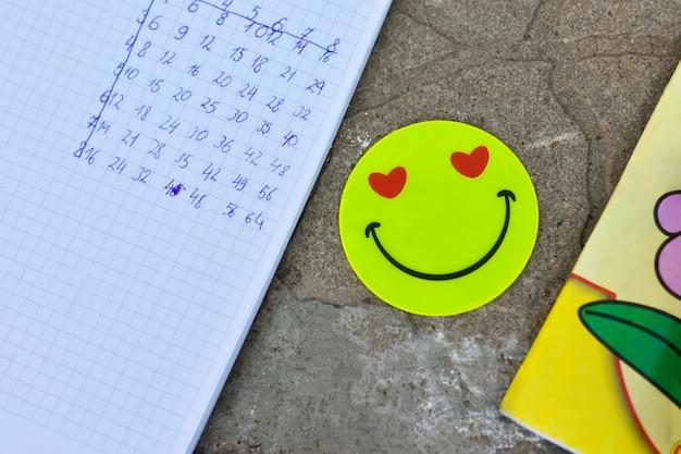 Schulhefte mit aufflackern emoticon auf fliesen im freien, vermehrungstabelle