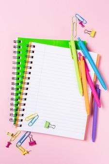 Schulhintergrund mit notizbüchern und buntem zubehör