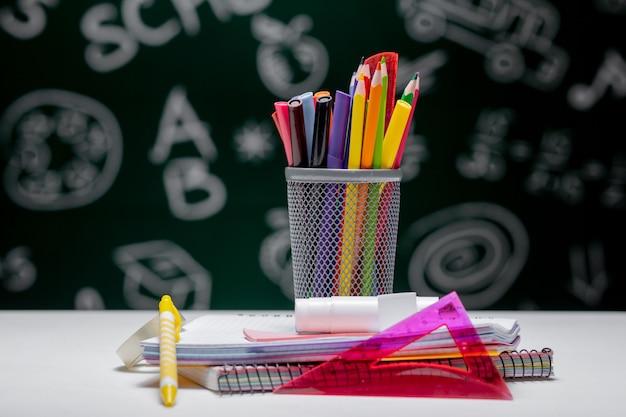 Schulhintergrund mit schreibwarenzubehör. bücher, globus, bleistifte und verschiedene büromaterialien, die auf dem schreibtisch auf einem grünen tafelhintergrund liegen