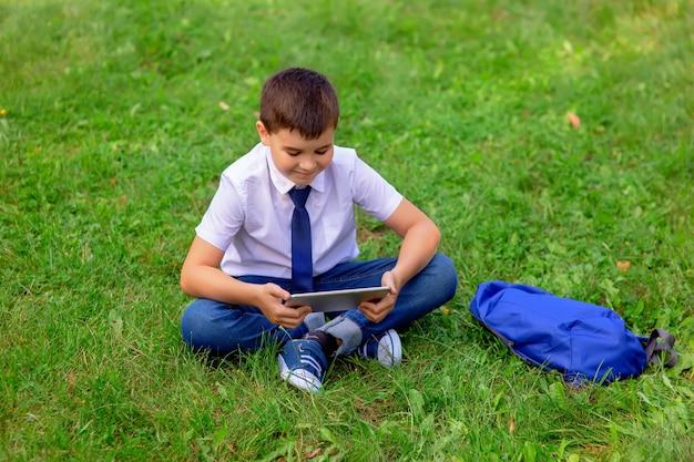 Schuljunge, der auf gras sitzt, während auf tablette schaut
