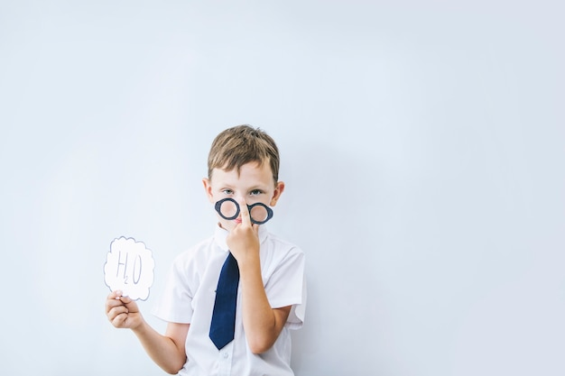 Schuljunge, der eine brille, ein weißes hemd und eine krawatte mit einem schild mit der chemischen formel des wassers trägt