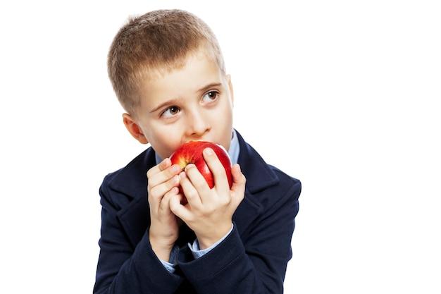 Schuljunge, der einen roten apfel isst. isoliert
