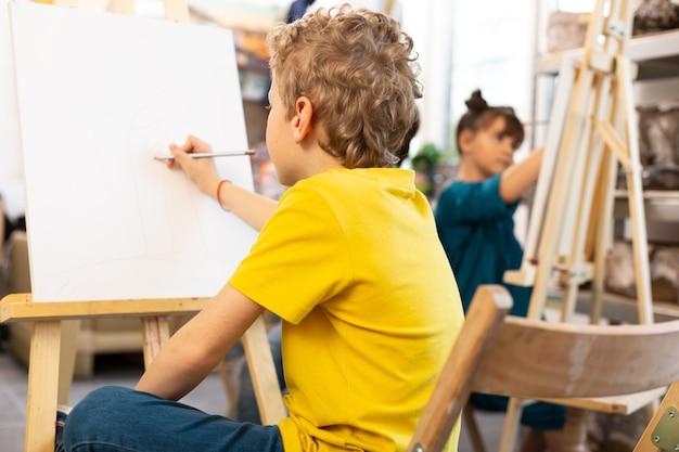 Schuljunge, der gelbe t-shirtzeichnung in der kunstschule trägt