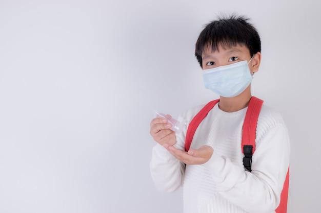 Schuljunge, der gesichtsmaske trägt und händedesinfektionsmittel anwendet. wiedereröffnung der schule nach covid-19-pandemie.