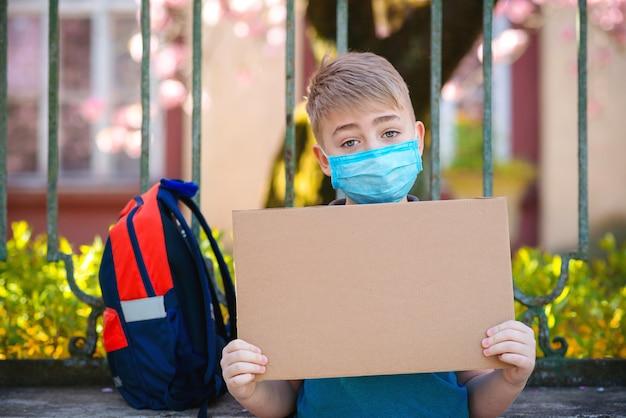 Schuljunge, der medizinische gesichtsmaske trägt. student mit rucksack im freien. junge hält leeres brett
