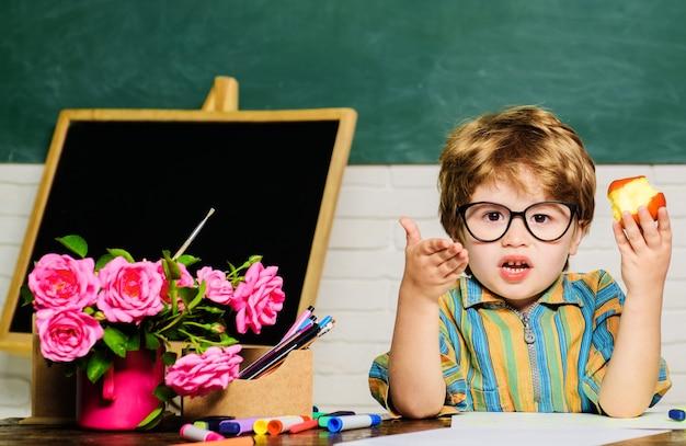 Schuljunge, der mit apfel zu mittag isst. gesundes essen für kinder. kleiner schüler während der mittagspause im klassenzimmer.