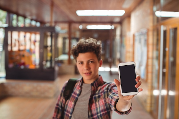 Schuljunge, der mit der schultasche steht, die handy im korridor an der schule zeigt
