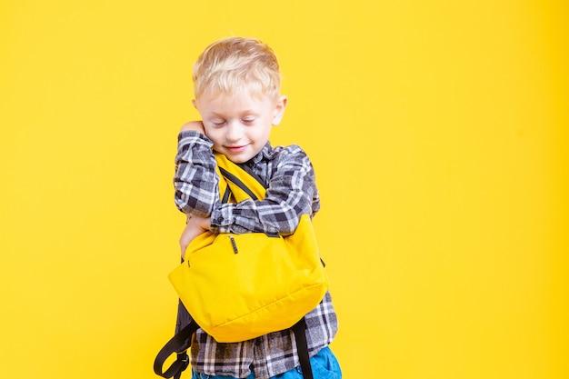 Schuljunge, der rucksack lokalisiert auf gelb hält.