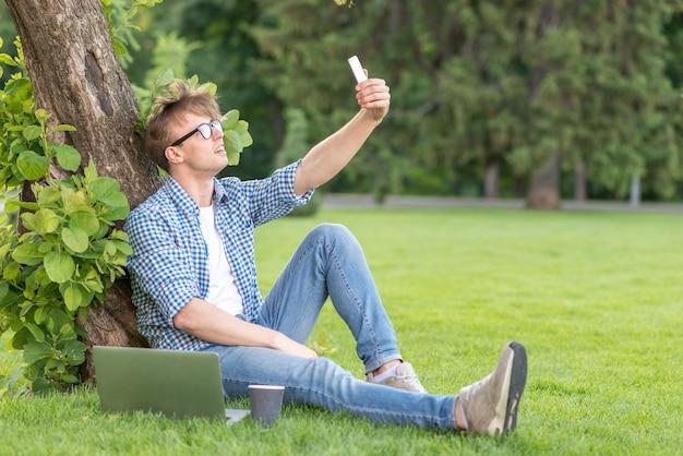 Schuljunge, der selfie im park nimmt
