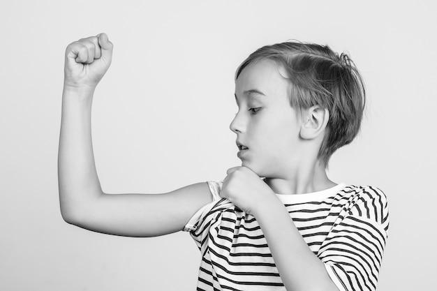 Schuljunge, der stärke und macht zeigt. netter junge, der seinen armmuskel zeigt. kindheit, fitness und sport. lustiges kind, das im studio aufwirft. erfolg, motivation und gewinnkonzept.