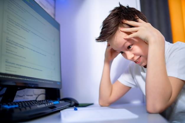 Schuljunge, der zu hause studiert. gestresstes kind mit kopfschmerzen für tests oder prüfungen am computer. lektionen lernen. konzept des bildungssystems.