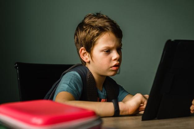 Schuljunge, der zu hause tablet spielt und mit technologie aufwächst