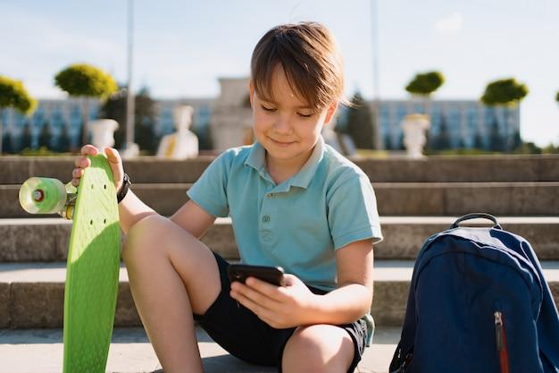 Schuljunge im blauen poloshirt, das auf der treppe mit einem blauen rucksack und grünem pennyboard unter verwendung des smartphones sitzt
