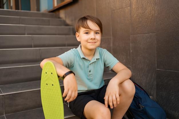 Schuljunge im blauen poloshirt sitzt auf der treppe mit einem blauen rucksack und grünem penny board