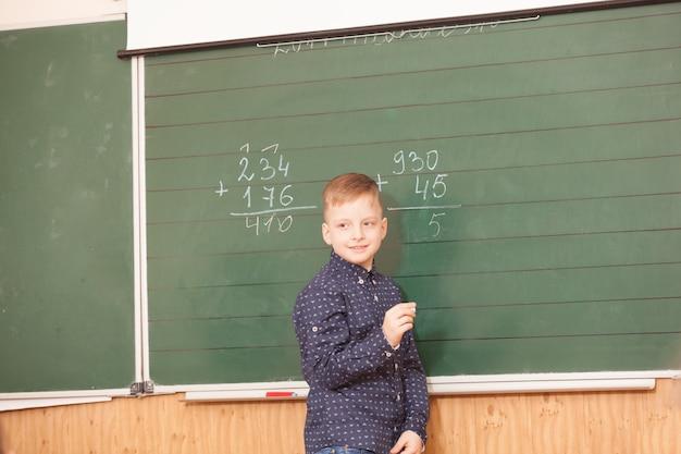 Schuljunge löst beispiele an der tafel im mathematikunterricht