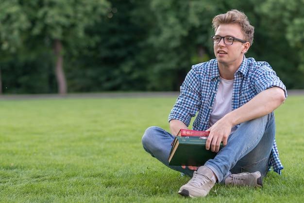 Schuljunge mit buch im park