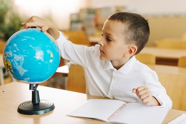 Schuljunge mit globus am schreibtisch
