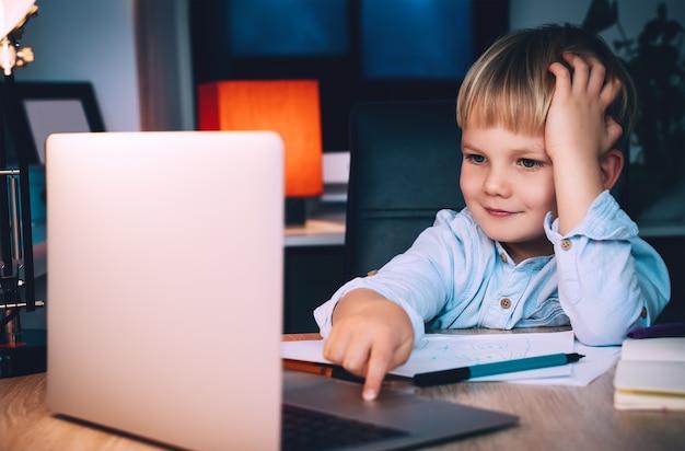 Schuljunge mit laptop am tisch zu hause kind mit digitaler technologie und internetkommunikation