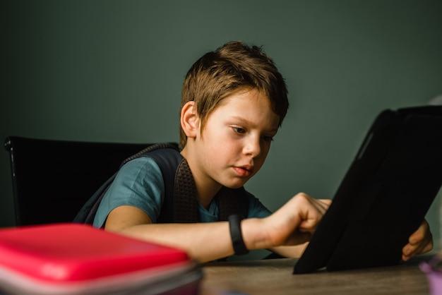 Schuljunge spielt tablette zu hause