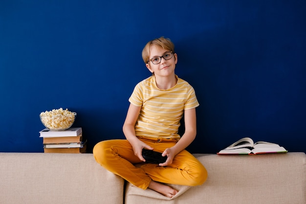 Schuljunge spielt videospiele hält ein gamepad isst popcorn anstatt lektionen zu lernen