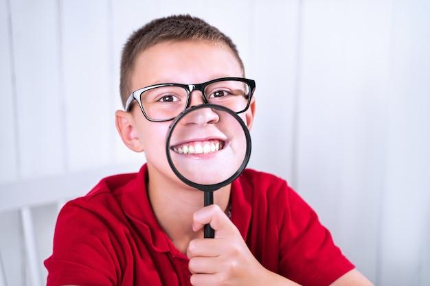 Schuljunge zeigt sein lächeln durch eine lupe